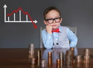 Boy in red bow tie sits with stacks of coins in front of him and a downward graph behind him.