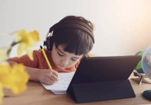Boy with headphones on holding a pencil doing homework in front of a tablet.