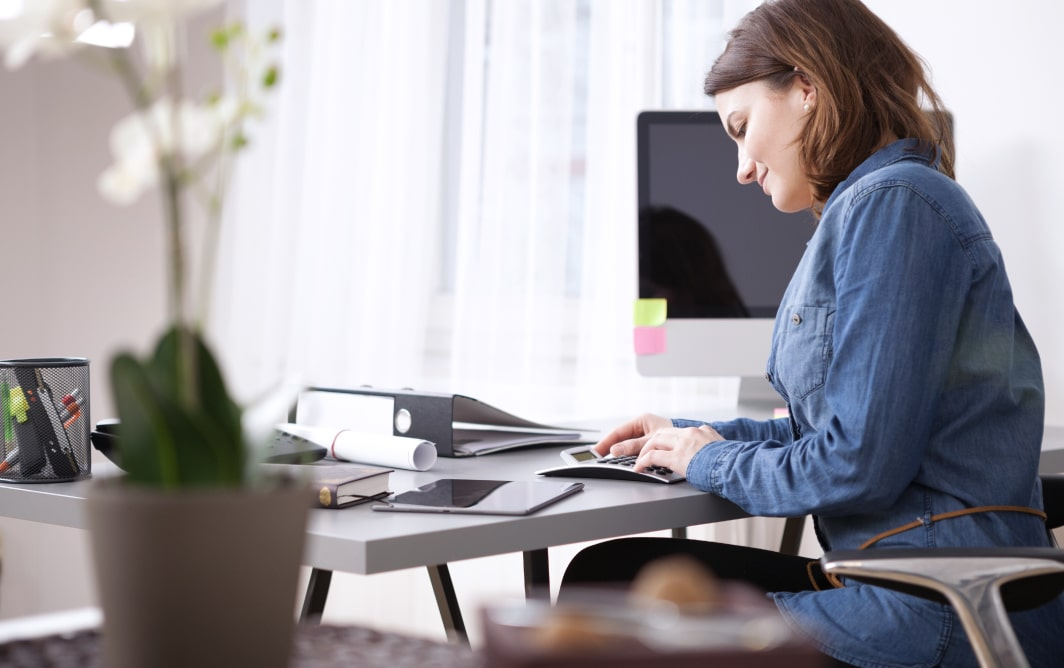 Woman checking credit score sitting at desk