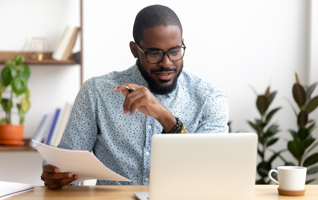Man reviewing documents on laptop.